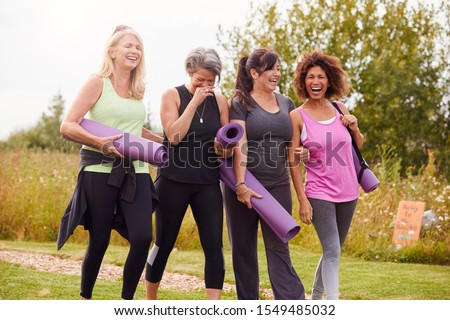 Group Of Mature Female Friends On Outdoor Yoga Retreat Walking Along Path Through Campsite #1549485032