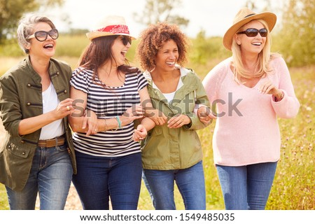 Group Of Mature Female Friends Walking Along Path Through Yurt Campsite Royalty-Free Stock Photo #1549485035