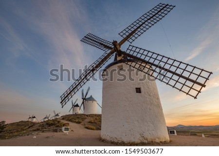 Beautiful white spanish windmill on the hill at first sunset lights near the castle in Consuegra, Toledo province, Spain #1549503677