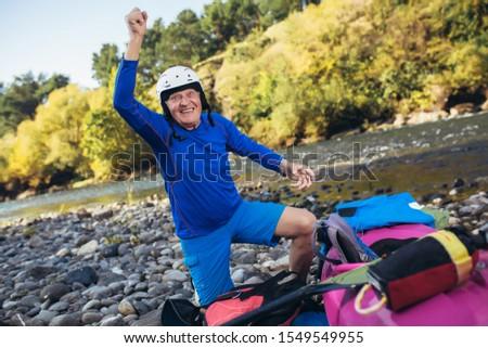 Senior man preparing for kayak tour on a mountain river. #1549549955