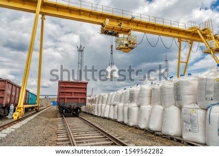 Cargo crane lifts two large bags of ammonium nitrate. Big yellow gantry crane. The work of lifting equipment in the warehouse. #1549562282