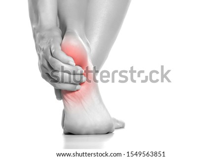 woman holding her painful heel on white background Royalty-Free Stock Photo #1549563851