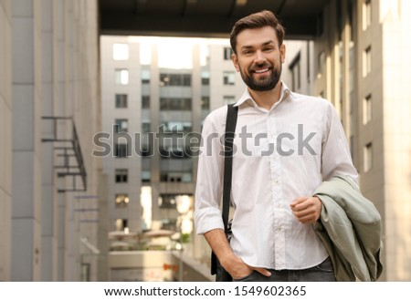Handsome man in stylish outfit on city street #1549602365
