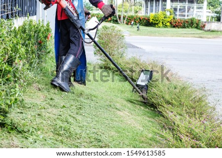 Worker cutting green grass with lawn mower string trimmer machine in the outdoor field. #1549613585