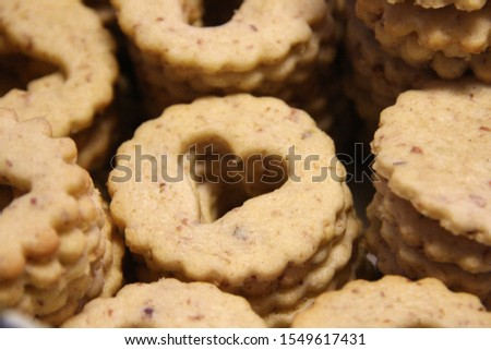Stacked shortbread biscuits for linzer biscuits lie on white paper Typical austrian christmas cookies recipe linzer biscuits #1549617431