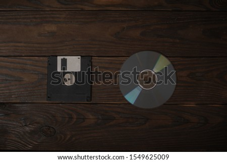 floppy disk and cd disk lie on a burnt wooden shield. concept art of transition of old media to new  #1549625009