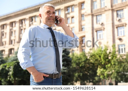 Handsome businessman talking by mobile phone in city, space for text #1549628114