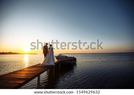 Beautiful bride and stylish groom together on the bridge against the background of the boat at sunset. Newlyweds tenderly hug, kiss and enjoy each other at sunset. Wedding. Love. Romantic moment.  #1549629632