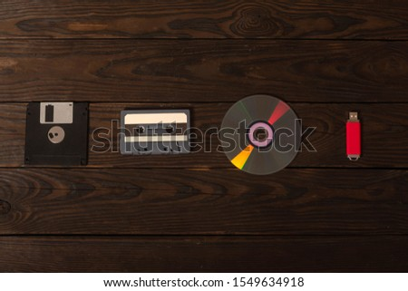 floppy disk, tape cassette , cd drive and flash drive are on a burnt wooden shield. concept art, progress in portable media #1549634918