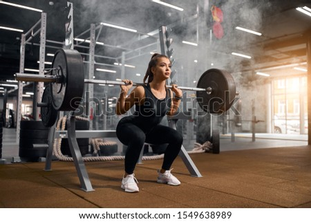 Beautiful young powerlifter squatting in modern fitness studio using heavy barbell, looking aside expressing self assurance, professional sport concept, white smoke in the air #1549638989