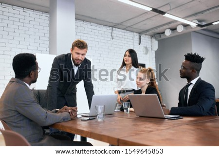 Demanding caucasian boss and his team working on one business project gathered to discuss problems on agenda #1549645853