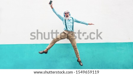 Senior crazy man jumping and listening music outdoor - Happy mature male celebrating and dancing outside - Joyful elderly lifestyle concept - Focus on his face Royalty-Free Stock Photo #1549659119