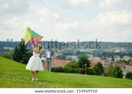 Bride and groom flying a kite together on a wedding day #154969910