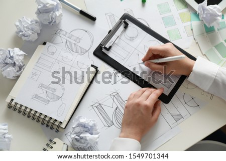 Female designer working at wooden table, top view