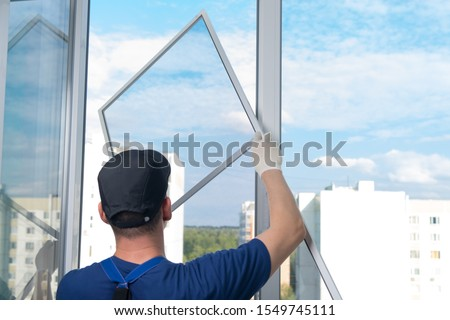 a worker in a blue uniform, rear view, installs a mosquito net in a plastic window frame, against the sky Royalty-Free Stock Photo #1549745111
