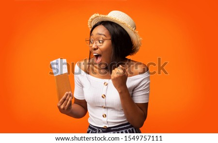 Cheap Flights. Excited Black Woman Traveler Holding Tickets And Passport Shaking Fists Standing On Orange Background. Studio Shot