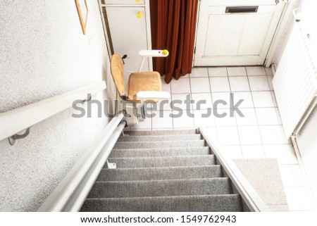 Automatic stair lift on staircase taking elderly people and disabled persons up and down in a house close-up #1549762943