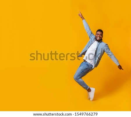 Funny african american man posing on tiptoes over yellow background in studio
