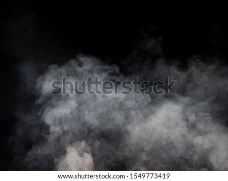 Clouds of smoke swirl on a dark background. Studio photography #1549773419