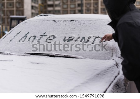A man in a winter jacket drawing i hate winter phrase on the car window. Winter negative, concept #1549791098