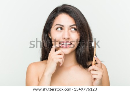 Young hispanic woman holding a toothbrush relaxed thinking about something looking at a copy space. #1549796120