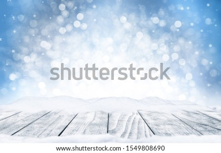 Decorative Christmas background with bokeh lights, snowflakes and empty old wooden table. Christmas and Happy New Year blue background with snowflake. Winter landscape with falling snow. #1549808690