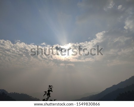 Sun hide itself with white clouds and looks a scenic pic from earth.