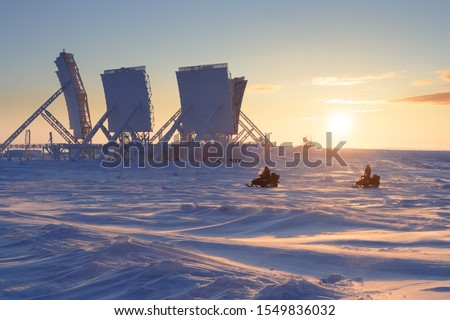 Winter arctic landscape with large antennas of an abandoned troposphere communication station. Snowmobiles ride on a tundra covered with snow. Beautiful golden lighting at sunset. Chukotka, Russia. #1549836032