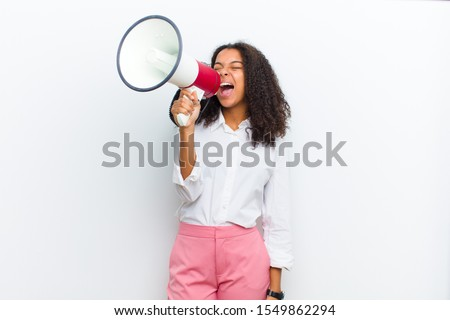 young pretty black woman with a megaphone against white wall #1549862294