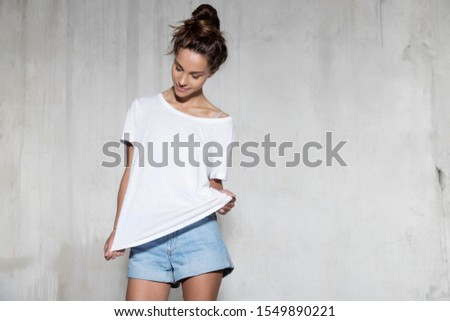 Beautiful young woman in comfortable summer clothes studio shot standing over concrete wall. Pretty girl teenager with cute hair bun wearing white t-shirt and jeans shorts. Summertime, hot weather #1549890221