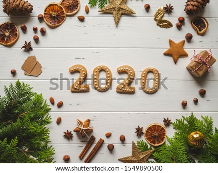 Gingerbread of the form of numbers 2020 new year ginger cookies, spices and firs on white wood background. Top view. #1549890500