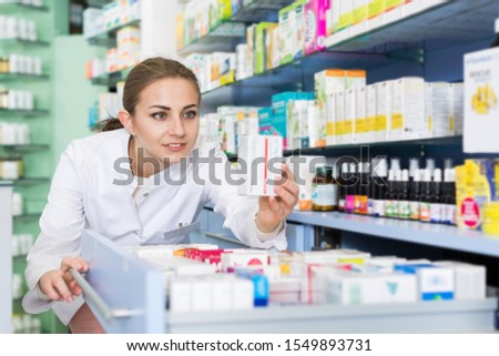Young woman pharmacist is attentively looking medicines in modern apothecary #1549893731