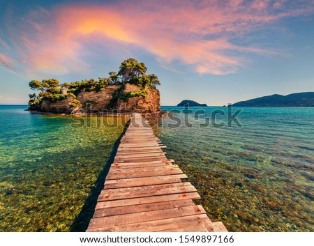 Superb summer sunrise on Port Sostis, Zakinthos island, Greece, Europe.  Wooden footbridge to Cameo Island. Beauty of nature concept background. #1549897166