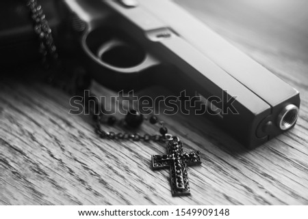 A black-and-white image of a gun that lies on a wooden surface along with a black Catholic cross, embodying war and religion.