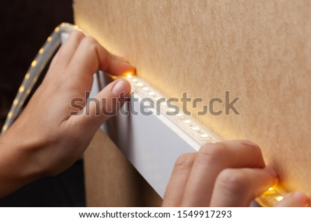 the master glues the LED strip into the niche of the shelf from the cabinet for lighting.installation of diode lighting tape. Royalty-Free Stock Photo #1549917293