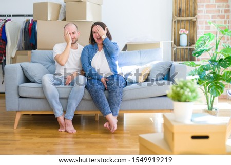 Young couple sitting on the sofa arround cardboard boxes moving to a new house covering one eye with hand, confident smile on face and surprise emotion. #1549919219