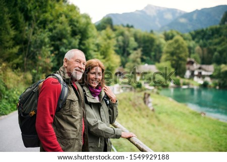A senior pensioner couple hiking in nature, resting. Copy space. #1549929188