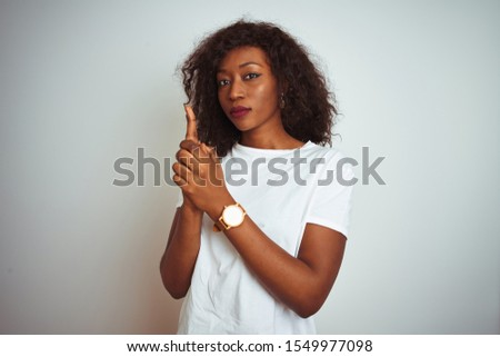 Young african american woman wearing t-shirt standing over isolated white background Holding symbolic gun with hand gesture, playing killing shooting weapons, angry face #1549977098