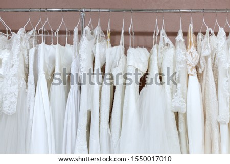 On the counter in the bridal salon are many beautiful white wedding dresses. #1550017010