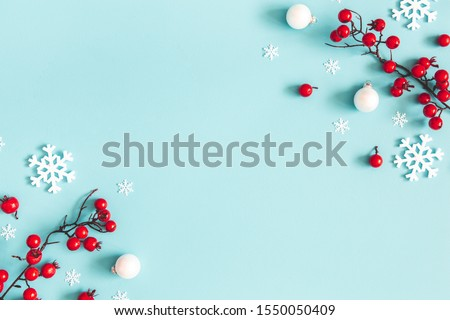 Christmas or winter composition. Snowflakes and red berries on blue background. Christmas, winter, new year concept. Flat lay, top view, copy space #1550050409