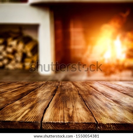 Rustic table top with blurred fireplace in luxurious home interior. Table background with empty space for products and decorations.