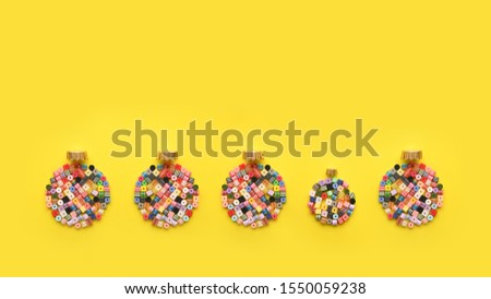 Christmas Bauble made of decoration elements on yellow background. Flat lay. Contemporary design. Contemporary art. Creative conceptual and colorful collage. #1550059238