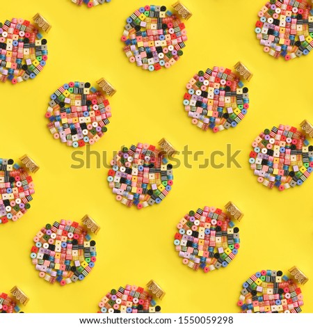 Christmas Bauble made of decoration elements on yellow background. Flat lay. Contemporary design. Contemporary art. Creative conceptual and colorful collage. #1550059298