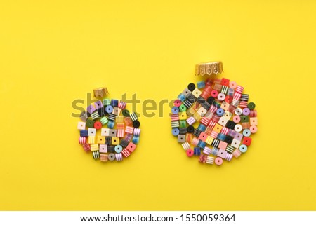 Christmas Bauble made of decoration elements on yellow background. Flat lay. Contemporary design. Contemporary art. Creative conceptual and colorful collage. #1550059364
