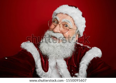 Portrait of cheerful Santa Claus holding selfie camera and smiling while posing against red background, copy space #1550095607