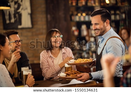 Happy waiter brining food to group of friends who are drinking beer in a tavern.  #1550134631