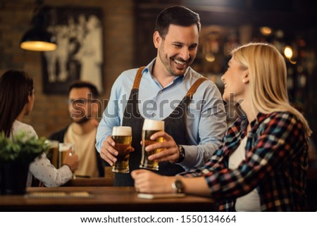 Happy waiter communicating with female guest while serving beer at her table in a bar.  #1550134664
