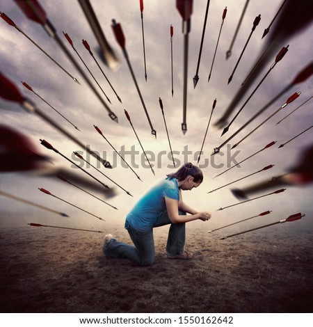 A woman is all alone and in prayer as she is surrounded by many arrows Royalty-Free Stock Photo #1550162642