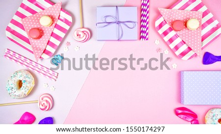 Colorful pink theme birthday party flat lay with snack, balloons, lollipops and gifts with negative copy space.