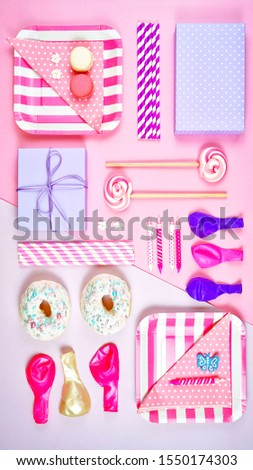 Colorful pink theme birthday party flat lay with snack, balloons, lollipops and gifts.
